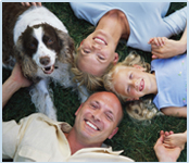 Family with dog laying in grass